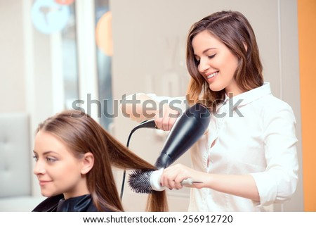 Stylish by professionals you can trust.  Mirror reflection of a young beautiful hairdresser doing her clients hair with a hair drier on the background of the hairdressing salon  - stock photo