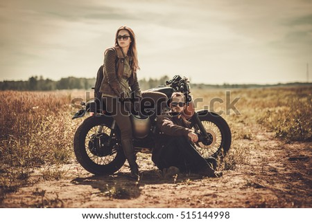Stylish cafe racer couple on the vintage custom motorcycles in a field.