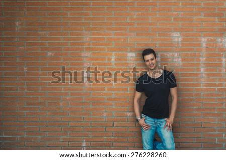 Stylish casual sexy man lean back brick wall. - stock photo