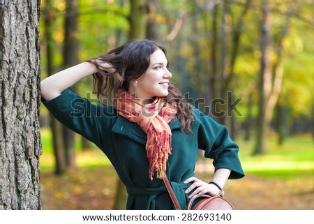 Stylish Caucasian Female Brunette Model Posing in Autumn Forest and smiling. Horizontal Image Composition - stock photo