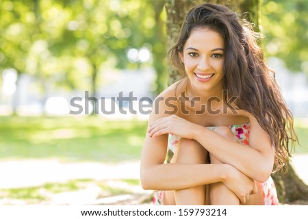 Stylish cheerful brunette sitting under a tree in a park on a sunny day - stock photo