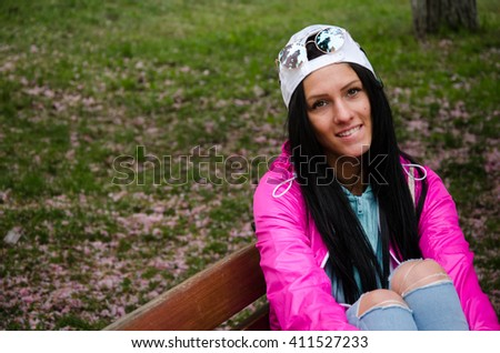 Stylish cheerful brunette sitting under a tree in a park on a sunny day