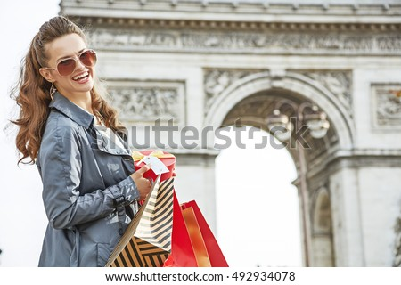 Stylish Christmas in Paris. Portrait of happy young woman in sunglasses with shopping bags and Christmas present near Arc de Triomphe in Paris, France
