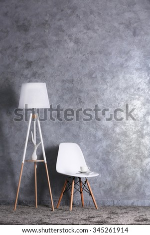 Stylish conception with chair and lamp on grey background - stock photo