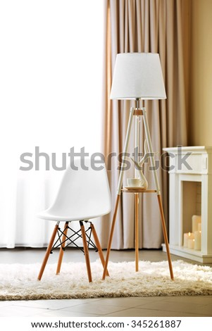 Stylish conception with chair and lamp on light room background