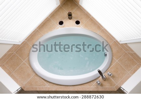 Stylish corner oval bathtub filled with fresh clean water in a brown tile surround flanked by two windows, overhead view - stock photo