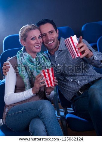 Stylish couple enjoying a movie together sitting in a cinema with their iconic striped containers of popcorn