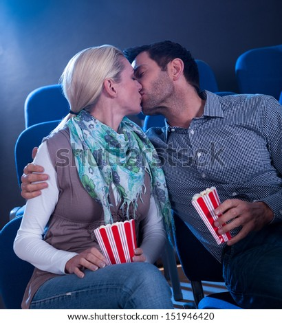 Stylish couple having romatic moment in a movie theater - stock photo