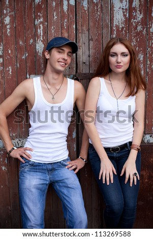 Stylish couple in jeans standing near wooden house. outdoor shot