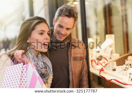 Stylish couple is looking at wedding rings. A grey hair man with beard and a woman with two shopping bags are standing in front of a jewelry shop. They are looking at the shop window.