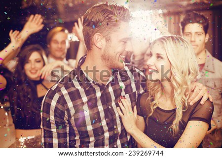 Stylish couple smiling and dancing together against flying colours - stock photo
