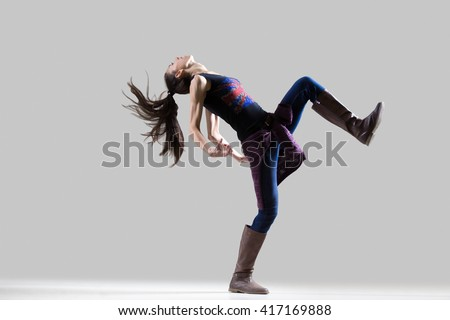 Stylish dancing young woman portrait. Fit sporty girl wearing English flag tank top warming up, working out with her long ponytail flying. Studio image. Grey background. Full length - stock photo