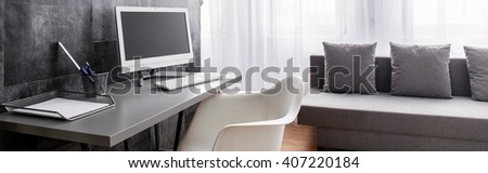 Stylish decorated office with desk and computer in modern spacious lounge