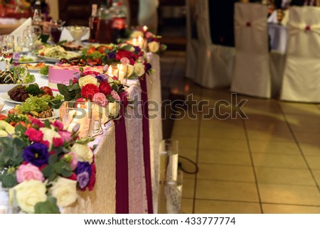 stylish decorated tables with bouquet of roses and food for wedding reception, catering in restaurant - stock photo