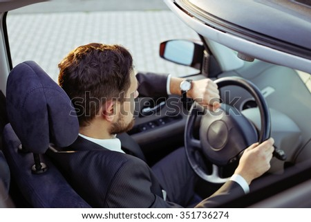 Stylish driver brunette with a beard wearing a black suit driving a car looking at his watch, hurrying to a business meeting. - stock photo