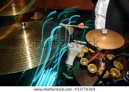 stylish drummer playing on a drums with a band on wedding reception with cool motion light - stock photo