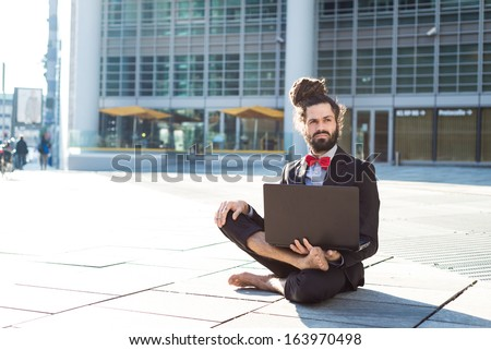 Stylish elegant dreadlocks businessman using notebook in business landscape - stock photo