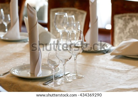stylish empty glasses and plates at setting at elegant table for wedding reception, catering in restaurant - stock photo