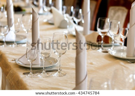 stylish empty glasses and plates at setting at elegant table for wedding reception, catering in restaurant