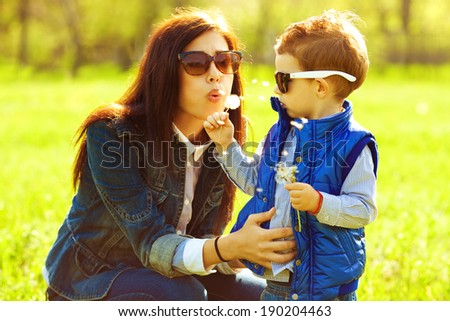 Stylish family concept. Portrait of fashionable baby boy and his gorgeous mother in trendy eyewear playing with dandelion in the park. Sunny spring day. Close-up. Outdoor shot