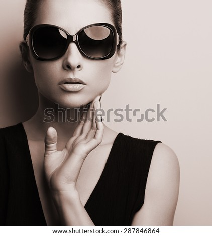 Stylish fashion female model in fashion sunglasses posing. Black and white color toned portrait - stock photo