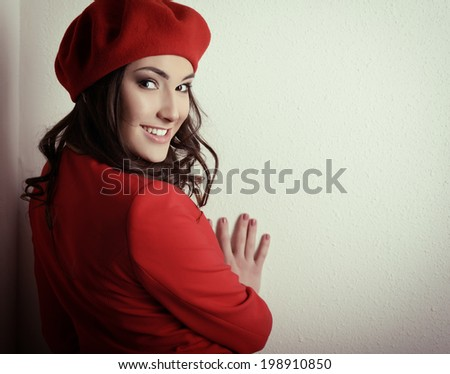 Stylish fashion girl in red suit and beret, posing at studio over white wall, toned - stock photo