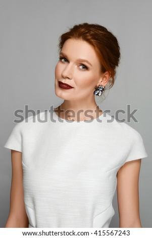 stylish fashion model with red mat lips and gemstone earrings. perfect skin, natural make up.