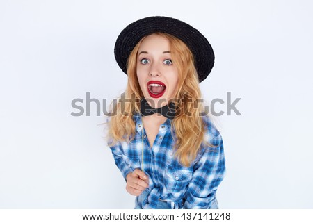 Stylish fashion portrait of trendy casual young woman in blue shirt and black hat holding a paper bow tie, Hipster blonde girl posing with surprised face isolated on white background.