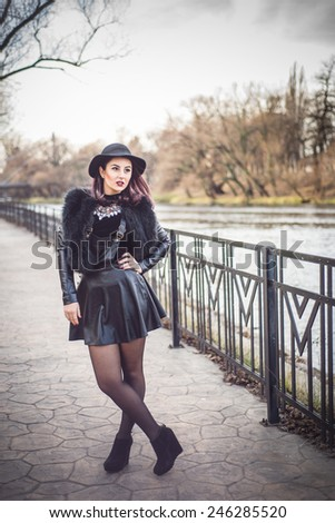 Stylish fashion Woman in trendy black leather and fur clothes. Turtle neck blouse and fedora hat - stock photo