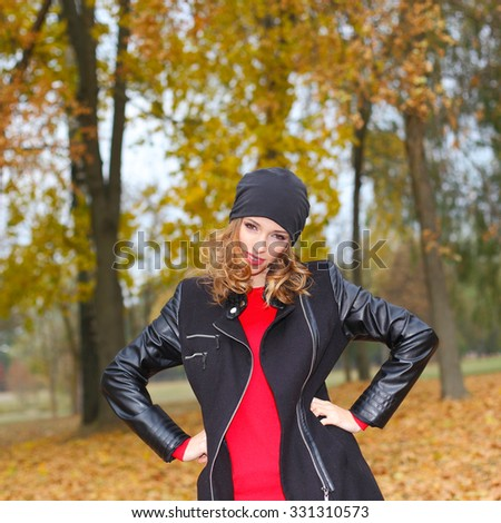 Stylish fashionable blonde girl hipster in the park in autumn. close emotional portraits hipster girl who shows obscene gestures on the background of fallen leaves