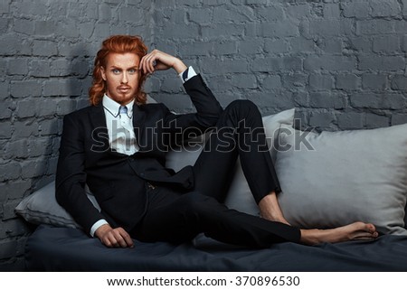 Stylish fashionable man with red hair and beard, lying on the sofa. - stock photo