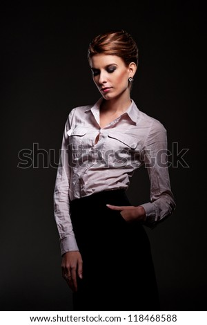 stylish female in white shirt posing over dark background - stock photo