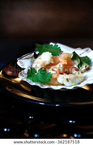 Stylish fine dining concept image for fish and seafood restaurants. garlic prawns sauteed in lazy chillies and served with garnish in scallop shells against a dark background. Copy space. - stock photo