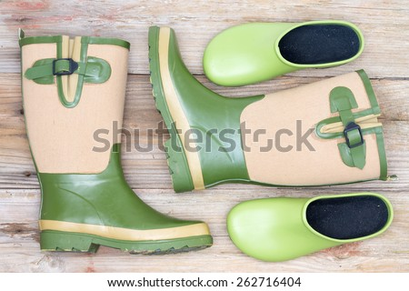 Stylish footwear for a fashionable gardener with green and beige decorative gumboots and green clogs lying on rustic wooden boards viewed from above - stock photo