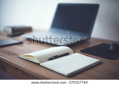 Stylish freelancer workspace with laptop open notepad work tools at home or studio office workplace - stock photo
