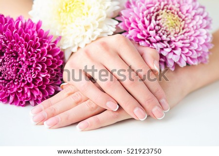 Stylish French manicure on fingernails and pink and white flowers