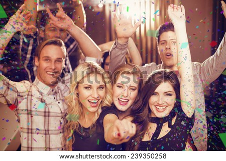 Stylish friends dancing and smiling against flying colours - stock photo