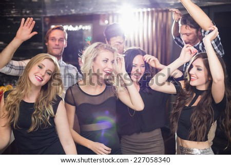 Stylish friends dancing and smiling at the bar