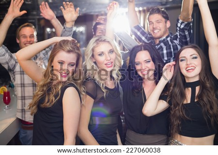 Stylish friends dancing and smiling at the bar - stock photo