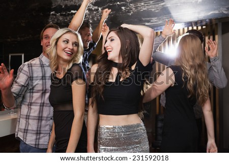 Stylish friends dancing and smiling at the nightclub - stock photo