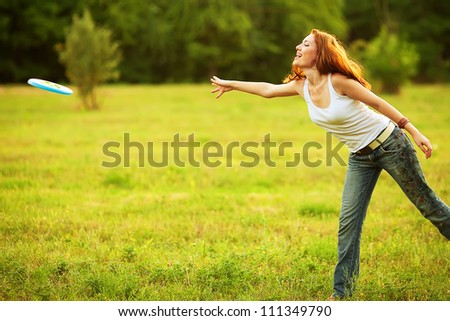 Stylish ginger girl having fun with frisbee in the park. Sunny summer day. Outdoor shot. - stock photo