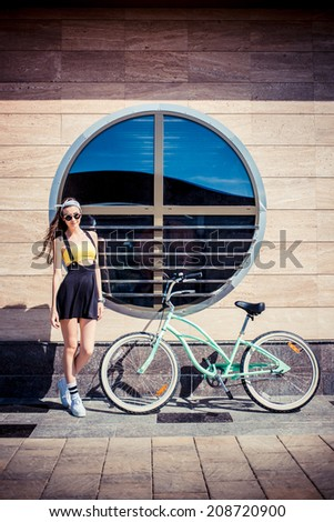 stylish girl hipster posing near cruiser bicycle against the background of the building with round windows