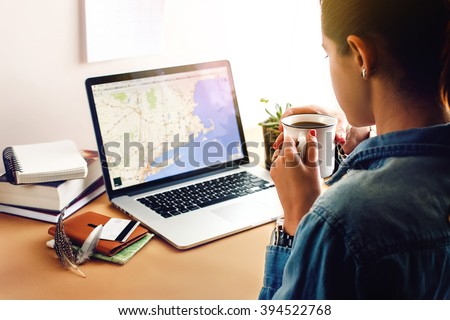 stylish girl holding coffee on background of laptop map card and succulent in morning light, summer travel and working home concept - stock photo
