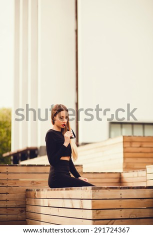 stylish girl in an elegant dress sitting in on the background of the city