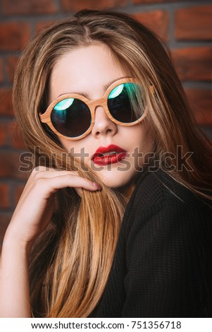 Stylish girl in black dress and round sunglasses posing by the brick wall. Modern youth fashion.