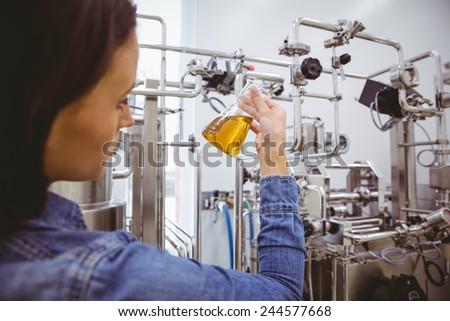 Stylish girl in denim jacket holding beaker of beer in the factory - stock photo