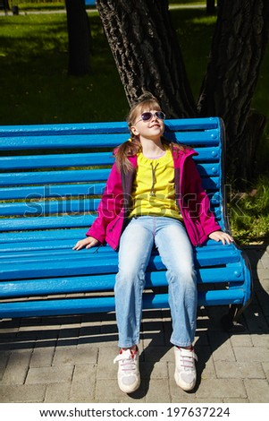 stylish girl in sunglasses sitting sitting on a park bench. children outdoors. vacation in the summer park - stock photo