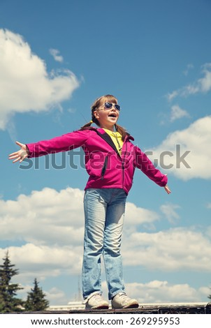 stylish girl in sunglasses standing on sky background. children outdoors. vacation in the summer park
