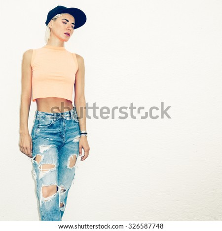 Stylish Girl in torn Jeans and a T-shirt Fashion - stock photo