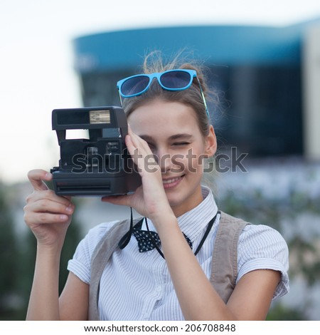 Stylish girl taking a photo in the city - stock photo